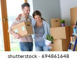 happy young couple unpacking or ... | Shutterstock . vector #694861648