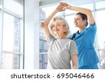 physiotherapist working with... | Shutterstock . vector #695046466