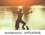 Small photo of The silhouette of the athlete is aimed at the target and shoots an arrow on the background of the lake. Archery.