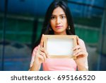 serious indian woman holding an ... | Shutterstock . vector #695166520