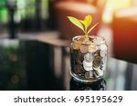 plant growing out of coins with ... | Shutterstock . vector #695195629