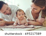 smiling young mother and father ... | Shutterstock . vector #695217589