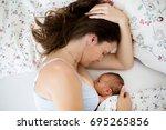 young mother breastfeeds her... | Shutterstock . vector #695265856