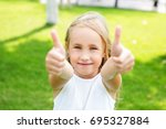 happy little girl showing... | Shutterstock . vector #695327884