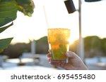 woman's hand holding an iced... | Shutterstock . vector #695455480