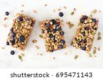 Stock photo superfood breakfast bars with oats and blueberries above view on white marble background 695471143