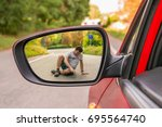 rearview mirror with a man hit... | Shutterstock . vector #695564740