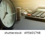 Small photo of Business Finance Accounting ,Tax calculation ,Interest calculation, Calculator Coin And Vintage clock on black floor