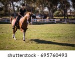 female jockey riding horse at... | Shutterstock . vector #695760493