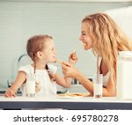 child with mother drinking milk.... | Shutterstock . vector #695780278
