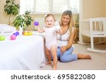 mother plays with the baby in... | Shutterstock . vector #695822080