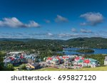 Small photo of Destination Mont Tremblant bird view of resort village in quiet relaxing early morning with painted buildings and colourful roofs under bright blue sky; white clouds over lake in Laurentian Mountains
