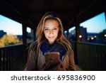 woman in the city at night... | Shutterstock . vector #695836900