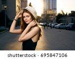 woman adjusting her hat against ... | Shutterstock . vector #695847106