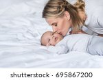 beautiful mother kissing her... | Shutterstock . vector #695867200
