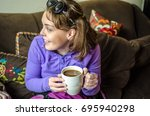 Small photo of An adult female looks to her side, laughing and smiling while holding a cup of coffee.