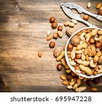 nuts with nutcracker in a bowl. ... | Shutterstock . vector #695947228
