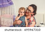 beautiful baby sitting on bed. | Shutterstock . vector #695967310