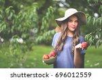 beautiful gardener girl picking ... | Shutterstock . vector #696012559