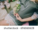 pregnant touching her belly | Shutterstock . vector #696060628