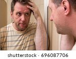 Small photo of The adult man frowned in displeasure and looked morosely at himself in the mirror. Wrinkles on the forehead of negative events