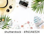 Small photo of Traveler accessories, tropical palm leaf branches on white background with empty space for text. Travel vacation concept. Summer background. Road frame set. Flat lay, top view.