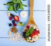 fruit salad on a wooden spoon | Shutterstock . vector #696148000