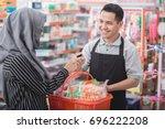 female customer paying her... | Shutterstock . vector #696222208