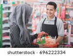 happy young male shopkeeper or... | Shutterstock . vector #696222334
