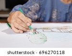 elderly woman painting color on ...   Shutterstock . vector #696270118