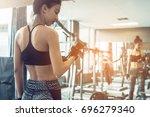 asian women lifting dumbbell in ... | Shutterstock . vector #696279340