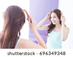young woman is combing hair in... | Shutterstock . vector #696349348