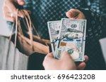 customer pays us dollar bills... | Shutterstock . vector #696423208