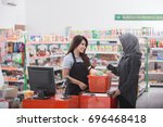 Small photo of female customer paying her bills with credit card at the cashier in supermarket
