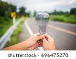 hold a transparent light bulb... | Shutterstock . vector #696475270