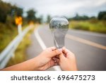 holds a clear light bulb to... | Shutterstock . vector #696475273