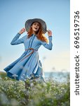 beautiful woman holding a hat... | Shutterstock . vector #696519736