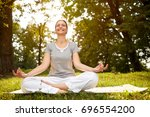 cheerful woman in lotus pose... | Shutterstock . vector #696554200