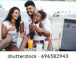 young mixed race family sitting ... | Shutterstock . vector #696582943