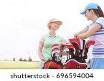 happy female golfers talking at ... | Shutterstock . vector #696594004