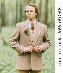 Small photo of The portrait of the handsome blond man in the vintage suit is buttoning hir jacket decorated with mini-bouquet.
