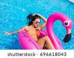 Tan Girl Sits On Inflatable...