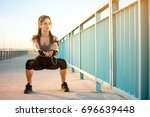 young woman doing squats on a... | Shutterstock . vector #696639448