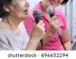 elderly woman sing a song with... | Shutterstock . vector #696652294