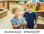 Stock photo toddlers boy and girl caresses and playing with turtle in the petting zoo concept of 696656209