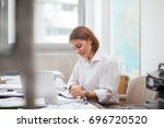 young woman working on laptop... | Shutterstock . vector #696720520