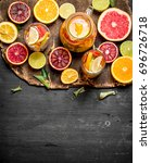Small photo of Citrus background. Fresh citrus juice with slices of limes, oranges, grapefruits and lemons. On black chalkboard.