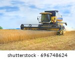 view on yellow working wheat... | Shutterstock . vector #696748624