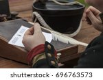 Hand of napoleonic epoch military clerk holding a quill pen. Recruiting soldiers.