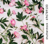Stock photo floral pattern made of pink peonies green leaves branches on white background flat lay top view 696789100